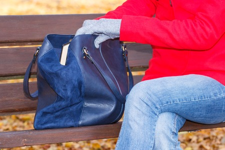 ladylike: Woman sitting on bench in autumn park, opening her handbag and searching different things in bag