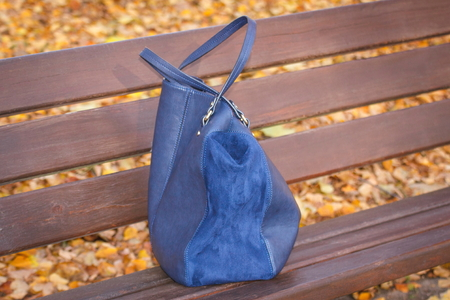 womanly: Womanly leather blue handbag lying on bench in autumn park Stock Photo