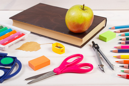 teaching crayons: Book, school accessories and orange leaves on white boards, autumn and back to learning concept