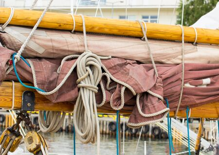 coiled rope: Yachting, parts of old wooden sailboat in port of sailing, coiled rope, sail, details of yacht