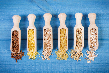 Various groats on wooden spoons lying on blue boards, concept of healthy food and nutrition
