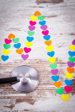 ecg heart: Electrocardiogram line of colorful paper hearts and medical stethoscope on old wooden rustic background, ecg heart rhythm, medicine and healthcare concept