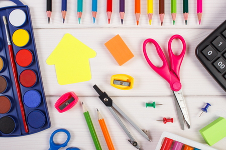 crayon  scissors: Office accessories, paper in shape of building on white boards, back to school concept