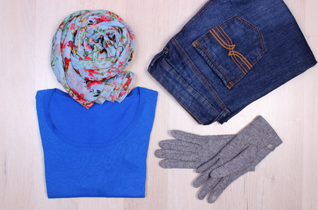 ladylike: Womanly clothes on wooden plank, gloves, sweater, shawl or scarf and pants, warm clothing for autumn or winter Stock Photo