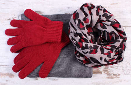 womanly: Woolen clothes for woman on old rustic board, womanly accessories, gloves shawl sweater, warm clothing for autumn or winter Stock Photo