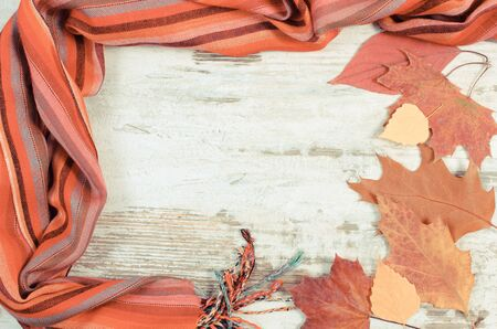 womanly: Vintage photo, Frame of womanly woolen shawl and autumnal leaves, copy space for text, warm clothing for autumn or winter
