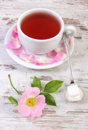 wild rose: Cup of hot tea with wild rose and blooming flowers on old rustic wooden background