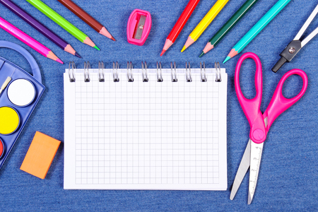 School and office supplies on jeans background, copy space for text or inscription in notepad, back to school concept