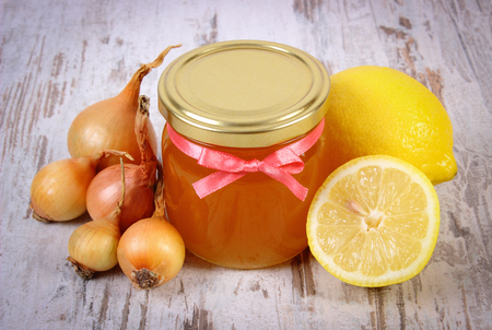 inmunidad: Fresh organic honey in glass jar, onions and lemon on old wooden background, healthy nutrition, strengthening immunity and treatment of flu
