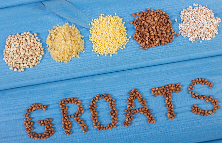 groats: Inscription groats and heap of various groats on blue boards, concept of healthy food and nutrition