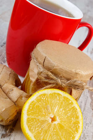 warming therapy: Lemon with honey in glass jar, fresh lemon, ginger and cup of hot tea on old rustic board, healthy food, strengthening immunity and alternative therapy Stock Photo