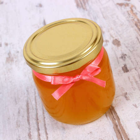 immunity: Fresh organic honey in glass jar on old rustic wooden background, healthy nutrition, strengthening immunity and treatment of colds and flu