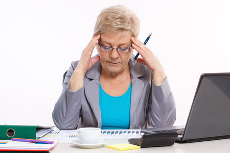 Elderly senior business woman holding hand on her head and analyzing financial charts at desk in office, analysis of sales plan Stock Photo