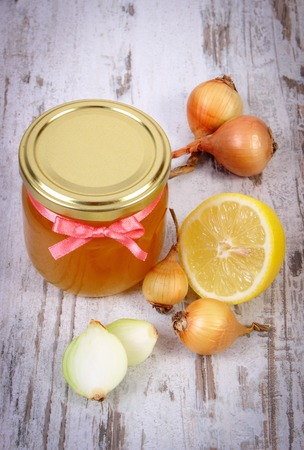 immunity: Fresh organic honey in glass jar, onions and lemon on old wooden background, healthy nutrition, strengthening immunity and treatment of flu
