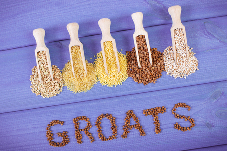 groats: Inscription groats and spoons with various groats on purple boards, concept of healthy food and nutrition