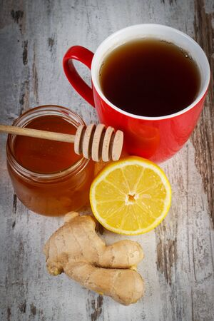 warming therapy: Fresh lemon, honey in glass jar, ginger and cup of hot tea on old rustic board, healthy food, strengthening immunity and alternative therapy