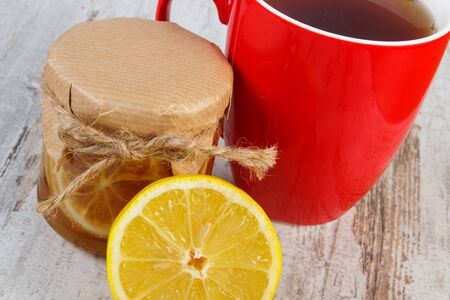 warming therapy: Lemon with honey in glass jar, fresh fruit and cup of hot tea on old rustic board, healthy food, strengthening immunity and alternative therapy