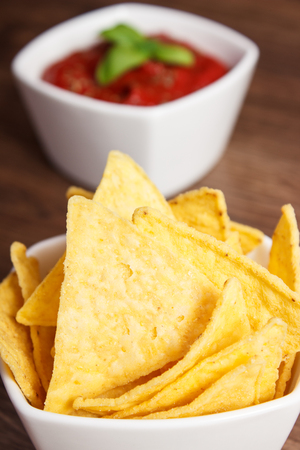 potato crisps: Crunchy salted potato crisps and sauce with basil in bowls on rustic board, concept of restriction eating unhealthy and salted food Stock Photo