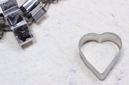 cookie cutters: Cookie cutters in shape of heart and set of cutters lying on white flour, accessories for baking