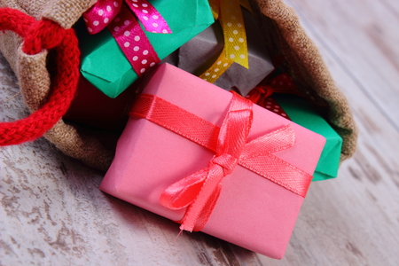 Wrapped colorful gifts for Christmas, birthday or other celebration in jute bag lying on old rustic board