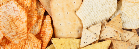 crisps: Heap of crunchy cookies and salted potato crisps with peppers, concept of restriction eating unhealthy and salted food Stock Photo