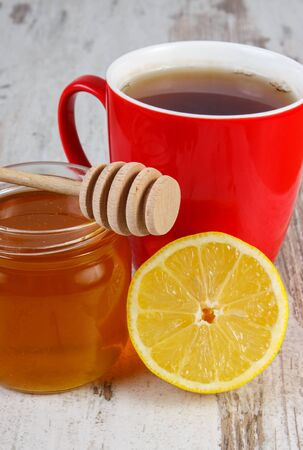 warming therapy: Fresh lemon, honey in glass jar and cup of hot tea on rustic board, healthy food, strengthening immunity and alternative therapy Stock Photo