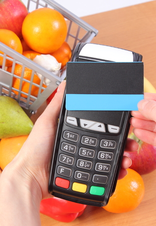 contactless: Hand using payment terminal with contactless credit card and fresh fruits and vegetables with plastic shopping carts, cashless paying for shopping