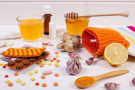 medical choice: Medical pills, hot water bottle and ingredients for preparation warming beverage for flu and cold, choice between tablets and alternative medicine Stock Photo