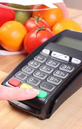 personal identification number: Using payment terminal, enter personal identification number, credit card reader and fruits and vegetables in paper shopping bag, cashless paying for shopping