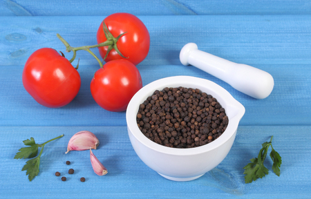 granule: Black pepper in white glass mortar and fresh vegetables on blue boards, seasoning for cooking