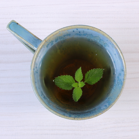 sedative: Leaf of green lemon balm in cup of calming herbal drink on white wooden table, sedative herbs, concept of healthy nutrition and herbalism Stock Photo