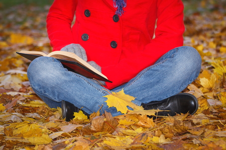 Woman In Red Coat Sitting On Orange Leaves Reading Book And