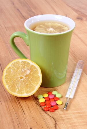 Pills, thermometer and hot tea with lemon for colds, treatment of colds, flu and runny Stock Photo