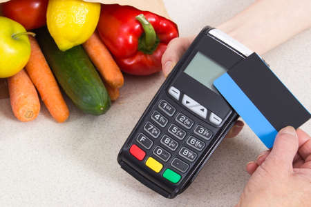 contactless: Hand of elderly senior woman using payment terminal with contactless credit card, cashless paying for shopping, fruits and vegetables Stock Photo