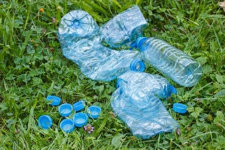 tirar basura: Botellas de pl�stico triturado de agua y tapas de botellas de minerales en el c�sped en el parque, el concepto de protecci�n del medio ambiente, basura del medio ambiente Foto de archivo