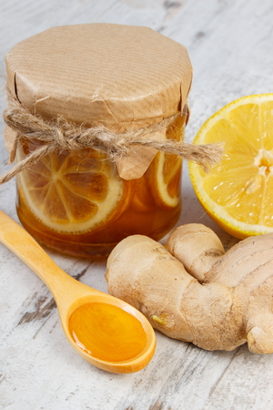 inmunidad: Lemon with honey in glass jar, fresh lemon, honey on wooden spoon and ginger on old board, concept of healthy food, nutrition and strengthening immunity