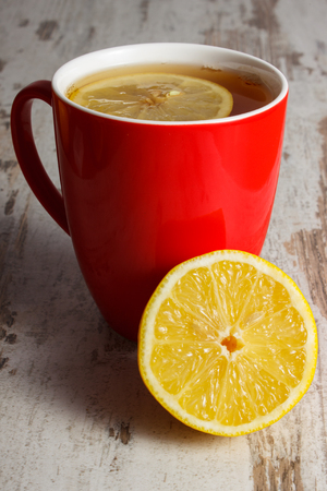 warming therapy: Fresh lemon and cup of hot tea with lemon on old wooden board, healthy nutrition, strengthening immunity and alternative therapy