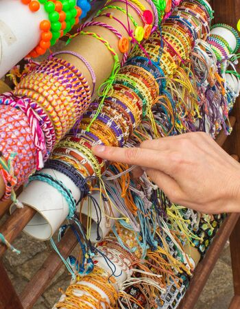 womanly: Hand of woman with colorful bracelets, shopping jewelry and womanly accessories on stall at the bazaar Stock Photo