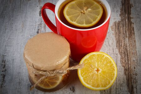 inmunidad: Lemon with honey in glass jar, fresh lemon and cup of hot tea on old wooden board, healthy food, strengthening immunity and alternative therapy