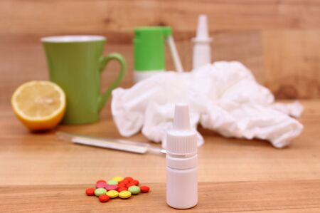 Pills and nose drops for colds, used handkerchiefs and hot tea with lemon in background, treatment of colds, flu and runny