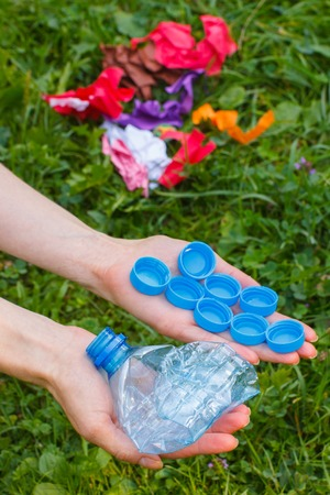 Hand of woman with plastic bottle and bottle caps, rubbish on grass in background, concept of environmental protection, littering of environment Stock Photo