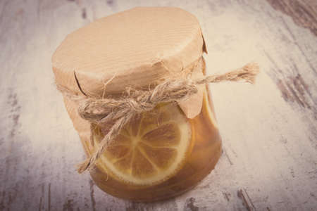 immunity: Vintage photo, Lemon with honey in glass jar lying on old wooden white table, concept of healthy food, nutrition and strengthening immunity