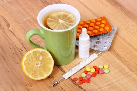 runny: Pills, nose drops and hot tea with lemon for colds, treatment of colds, flu and runny Stock Photo