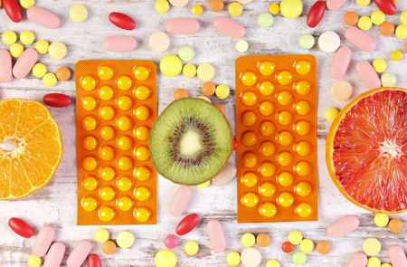 Fresh natural fruits and pills, tablets or capsules, choice between healthy nutrition and medical supplements