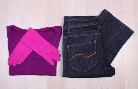 warm shirt: Pair of gloves, sweater or shirt and pants for woman on wooden surface plank, womanly accessories, warm clothing for autumn or winter