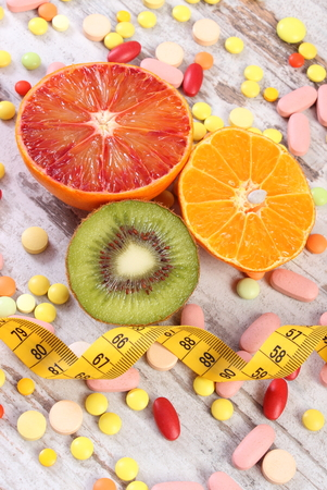 medical choice: Fresh fruits, tape measure, pills, tablets and capsules on rustic wooden background, concept of slimming and choice between healthy nutrition and medical supplements Stock Photo