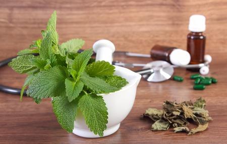 herbalism: Fresh green lemon balm in white mortar, stethoscope and medical capsules, choice between pills and alternative medicine, healthy lifestyle, herbalism