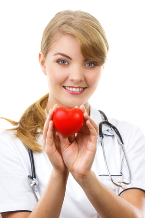 the cardiologist: Smiling woman doctor cardiologist in white apron with stethoscope holding red heart, healthcare and medicine concept, white background