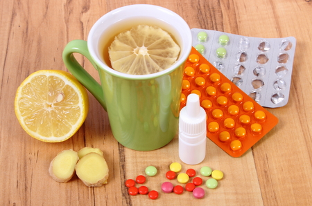 colds: Pills, nose drops and hot tea with lemon and ginger for colds, treatment of colds, flu and runny Stock Photo