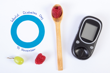 medical fight: Glucose meter, fresh ripe fruits and blue circle of paper, symbol of world diabetes day. White background